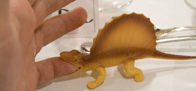 Dinosaur toy biting a finger