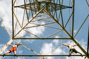 Power line tower with two men climbing it