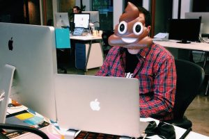 Developer with poop emoji mask on