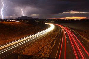 Long exposure shot of cars on the highway with lightning in the background