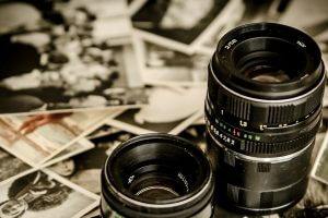 Camera lenses sitting on photos