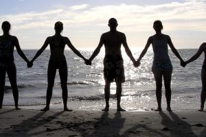 People holding hands on a beach