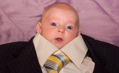 A baby in an adult-sized suit